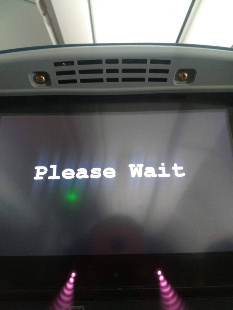 "An airplane television screen, the kind on the seatback in front of you displays letters in white print that reads ""Please Wait"""